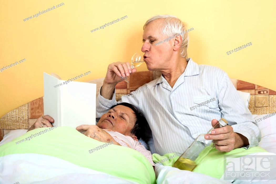 Stock Photo: Funny senior couple relaxing in bed with alcohol and book.