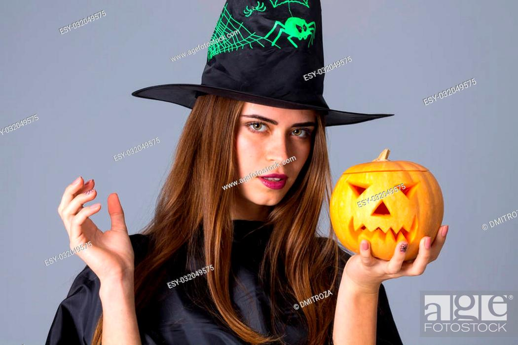 Stock Photo: Pretty young woman in black costume of witch with black hat holding a pumpkin on blue background in studio.