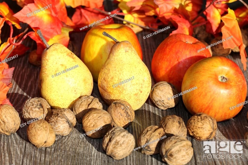 Stock Photo: Apples, pears and wal nuts on a rustic wooden table as autumn motif.