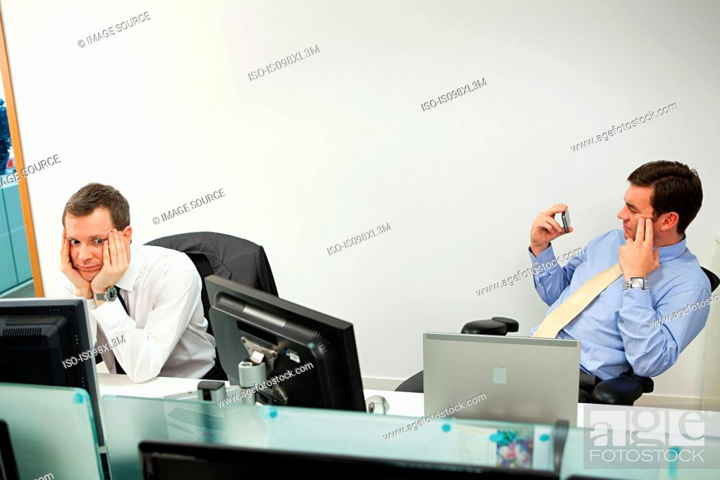 Stock Photo: Businessman using smartphone, male colleague looking sideways.