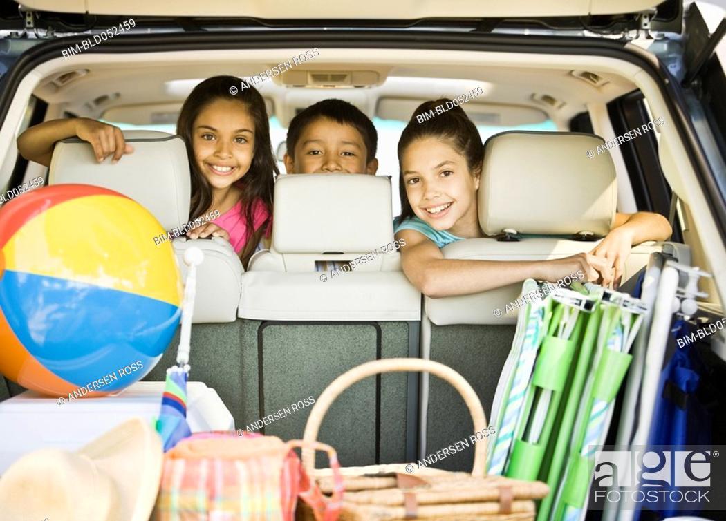 Stock Photo: Hispanic siblings sitting in car.