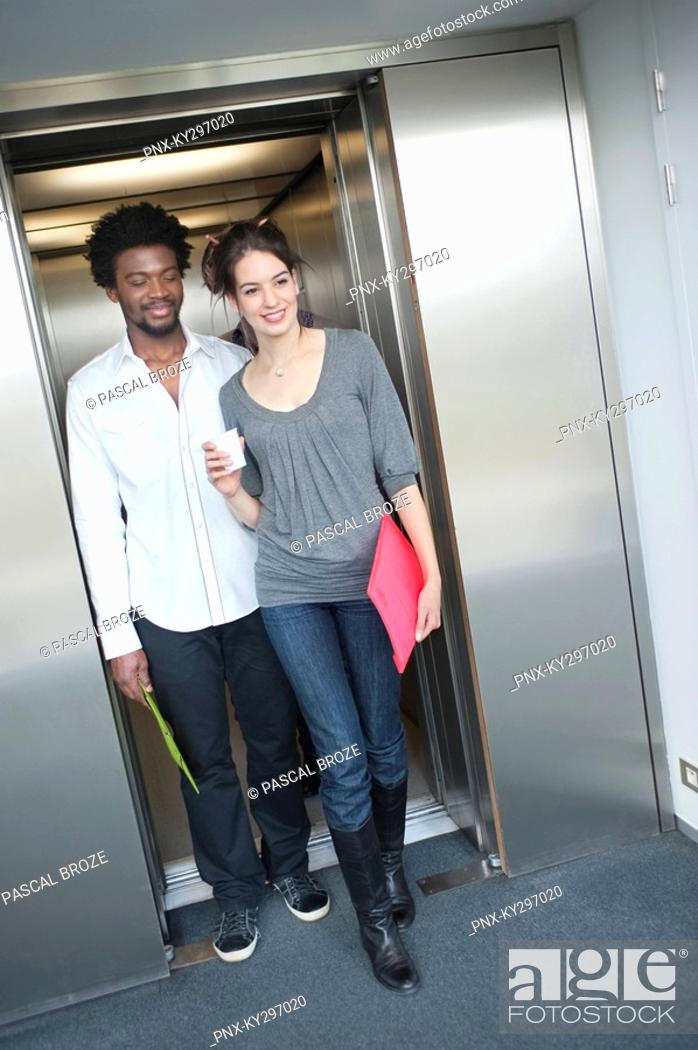 Stock Photo: Businesswoman coming out from an elevator with her colleague.