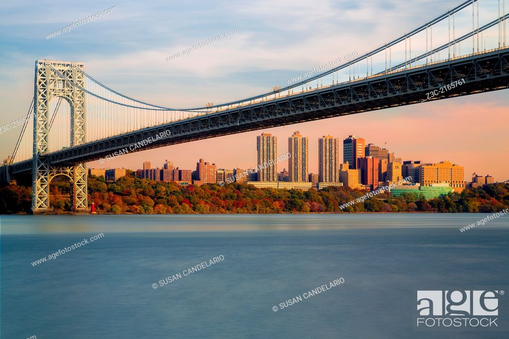 Stock Photo: Wide view of the George Washington Bridge with the New York City skyline during Autumn. Jeffrey's Hook Lighthouse also know as the Little Red Lighthouse can be.