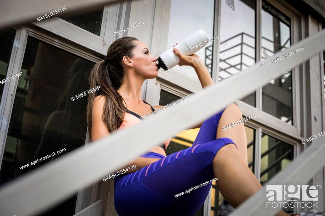 Stock Photo: Caucasian woman drinking water on urban staircase.