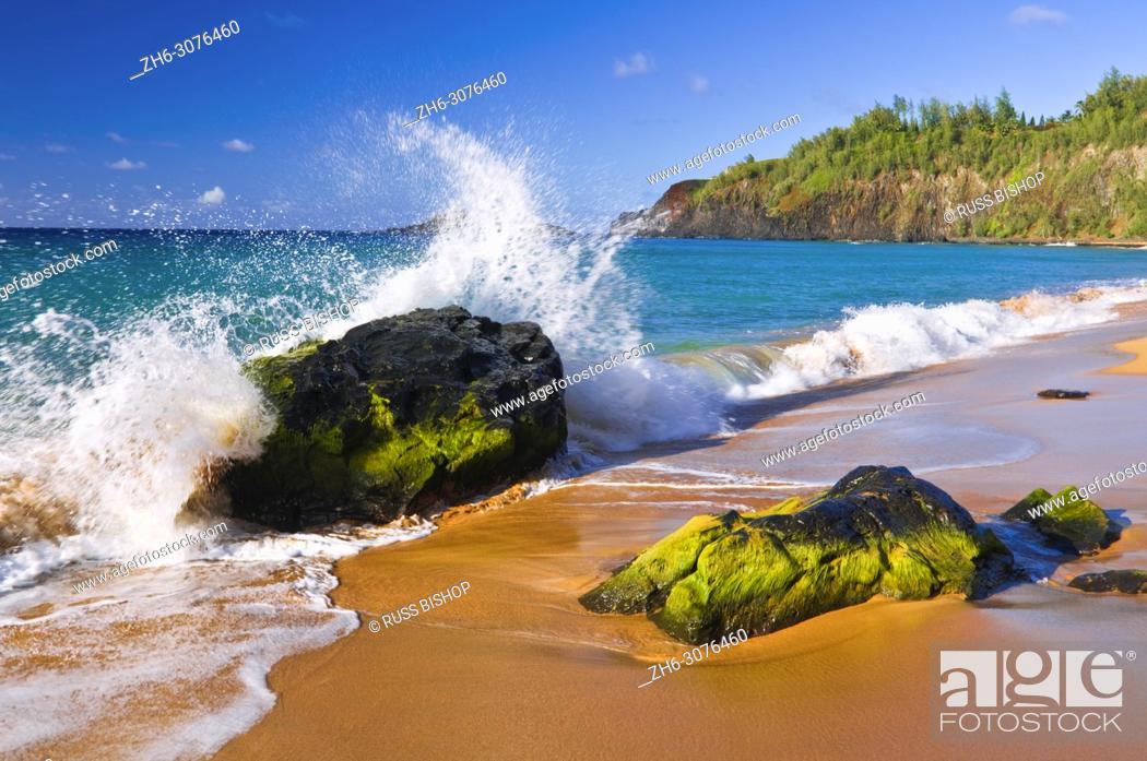 Stock Photo: Surf crashing on lava rocks at Secret Beach (Kauapea Beach), Kilauea Lighthouse visible, Island of Kauai, Hawaii USA.