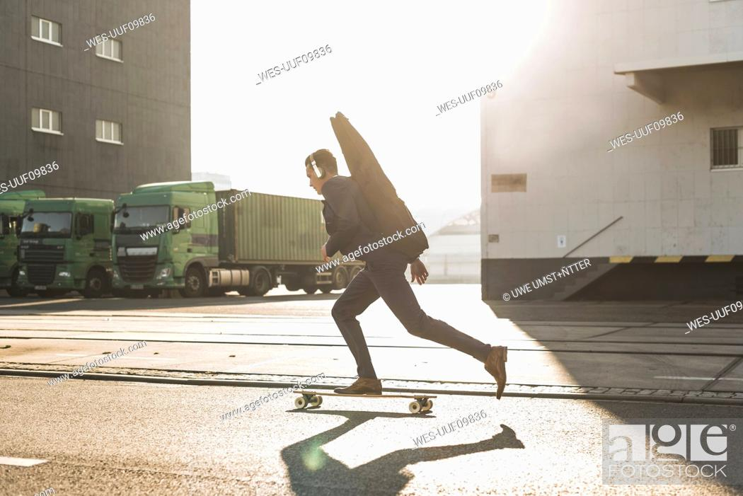 Imagen: Young man with guitar case riding skateboard on the street.