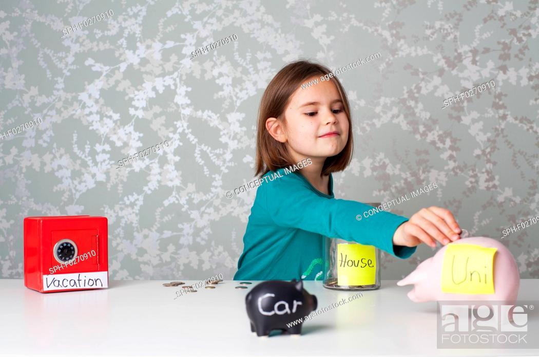 Stock Photo: Girl putting money into piggy banks.