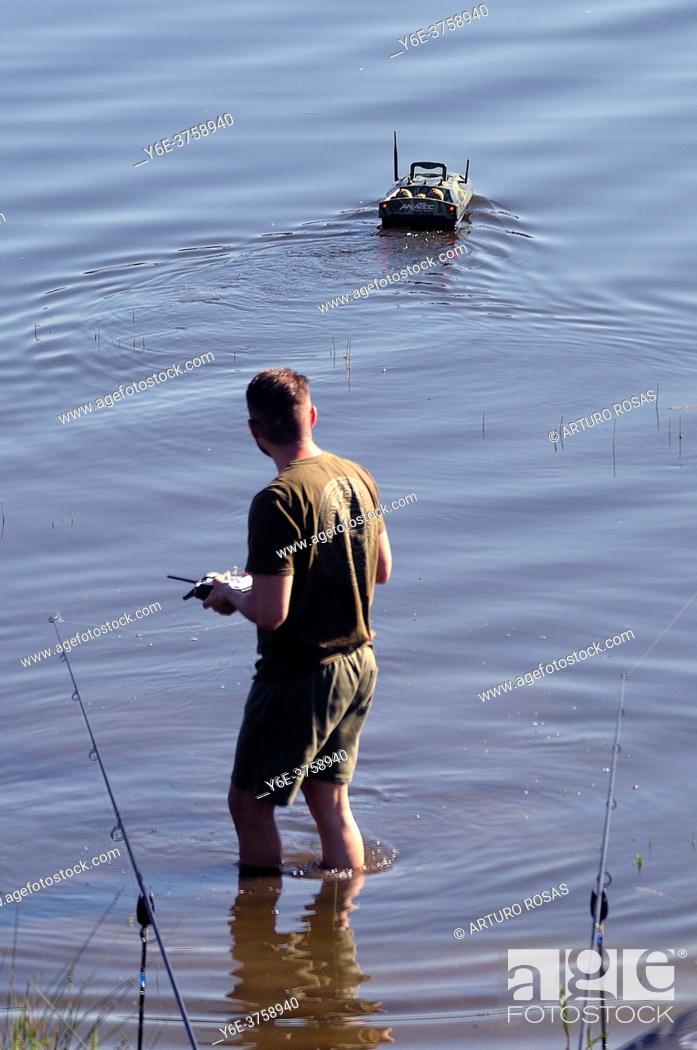 Stock Photo: Fisherman with a remote-controlled boat. Guadalix de la Sierra, MAdrid.