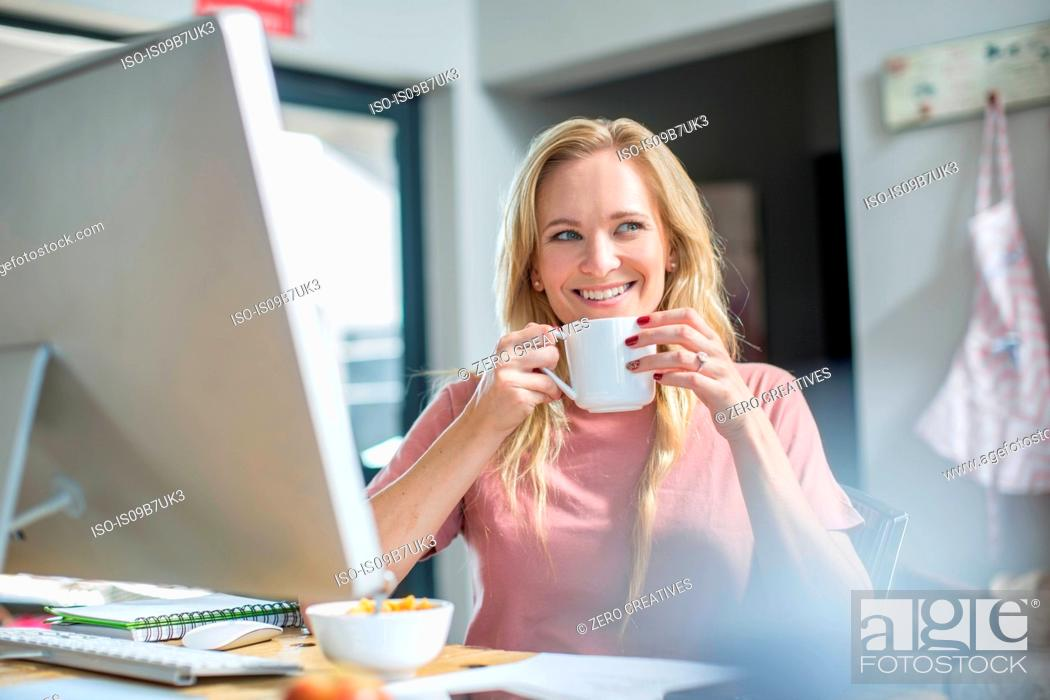 Stock Photo: Woman at computer drinking coffee smiling.