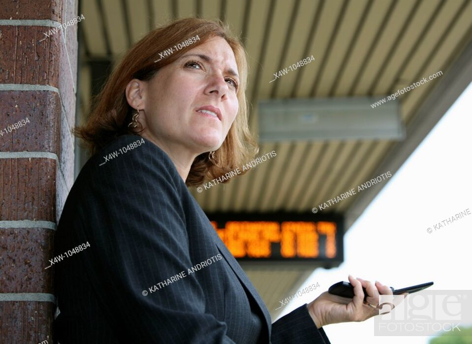 Stock Photo: Businesswoman standing on platform hold her cell phone with train timetable in background awaiting the arrival of her commuter train on her way to work.