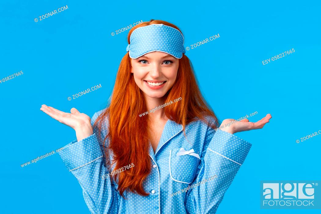 Stock Photo: Who knows, dont care. Carefree and unbothered happy smiling redhead female in nightwear, sleep mask, shrugging indecisive and clueless with hands raised.