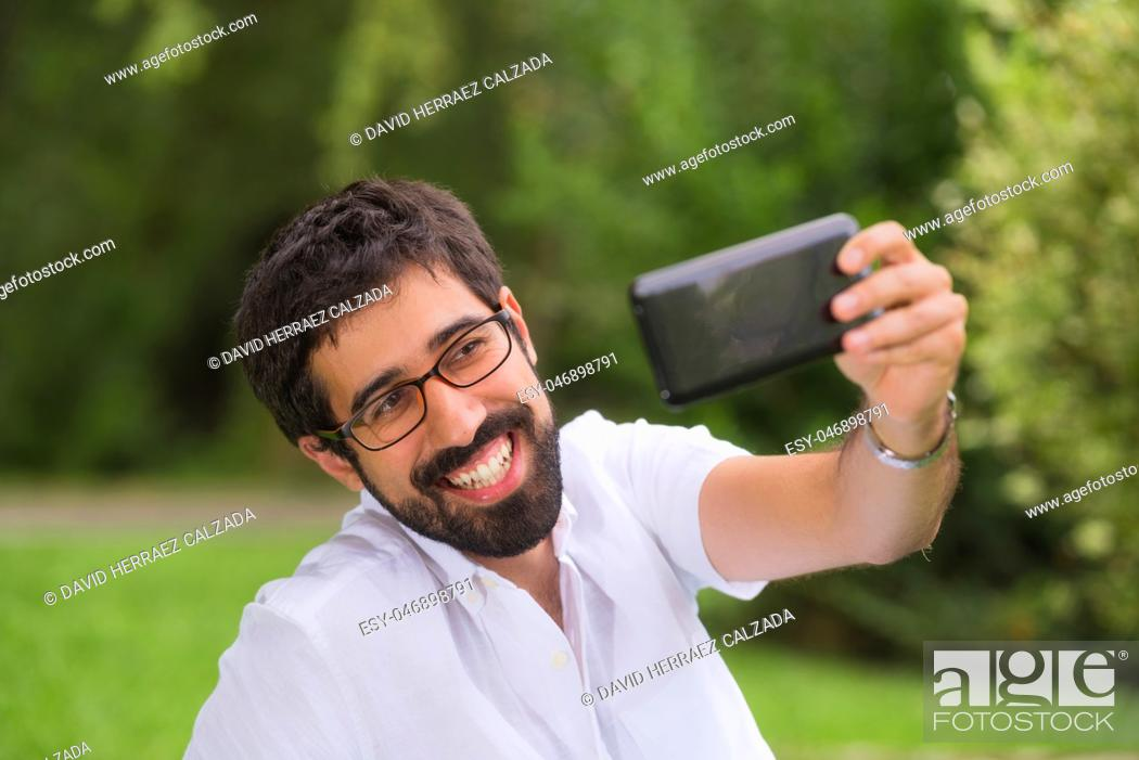 Photo de stock: Happy Young man taking a selfie in the park.