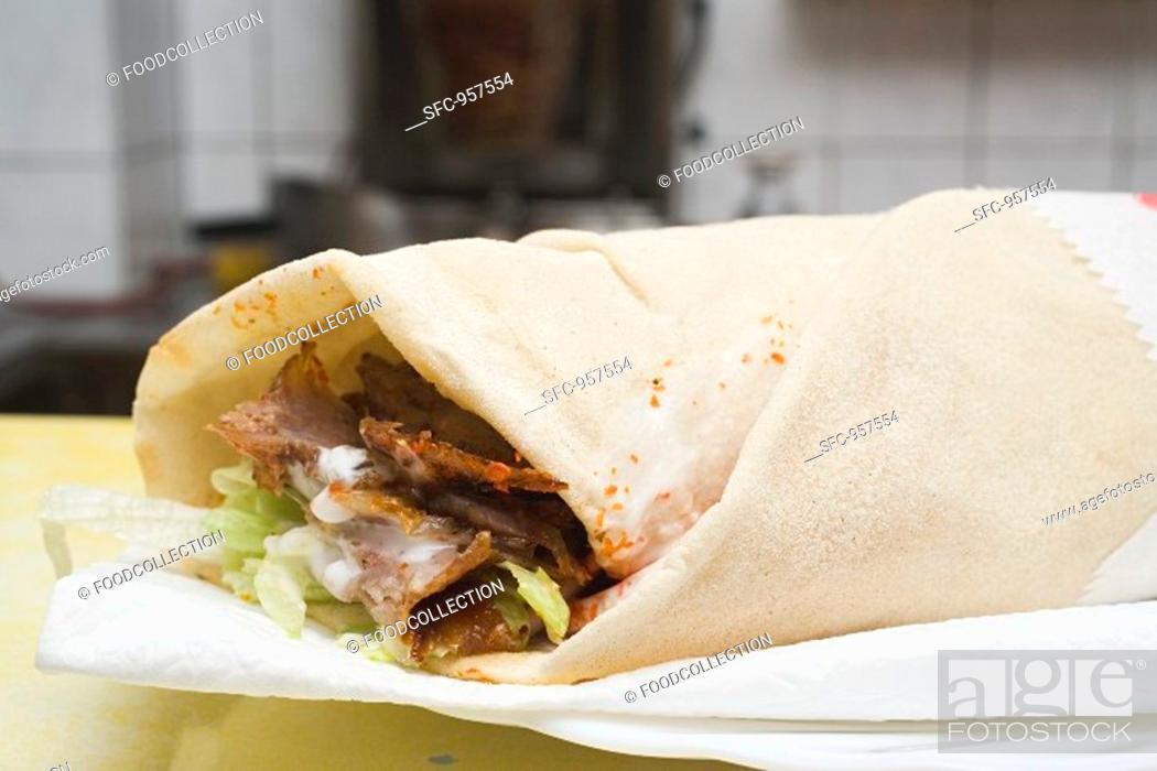 Stock Photo: Döner wrap on paper napkin in snack bar.