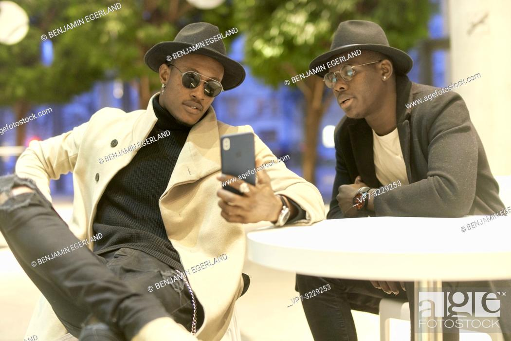Stock Photo: two men sitting indoors at table using smartphone, explaining, showing, meeting, discussion, conversation.