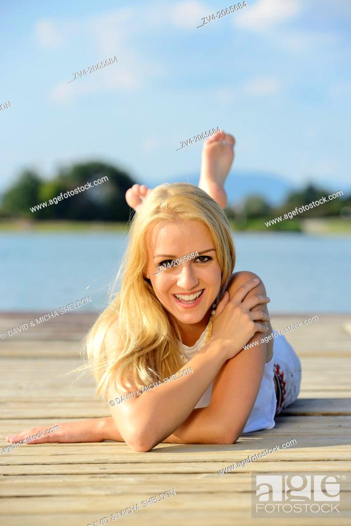 Stock Photo: Young woman lying on a jetty at a lake in Austria.
