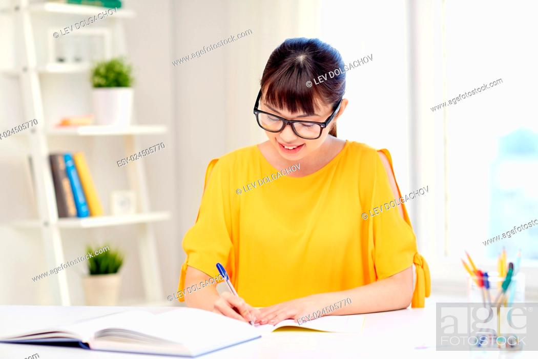 Stock Photo: people, education, high school and learning concept - happy asian young woman student in glasses with book and notepad writing at home.