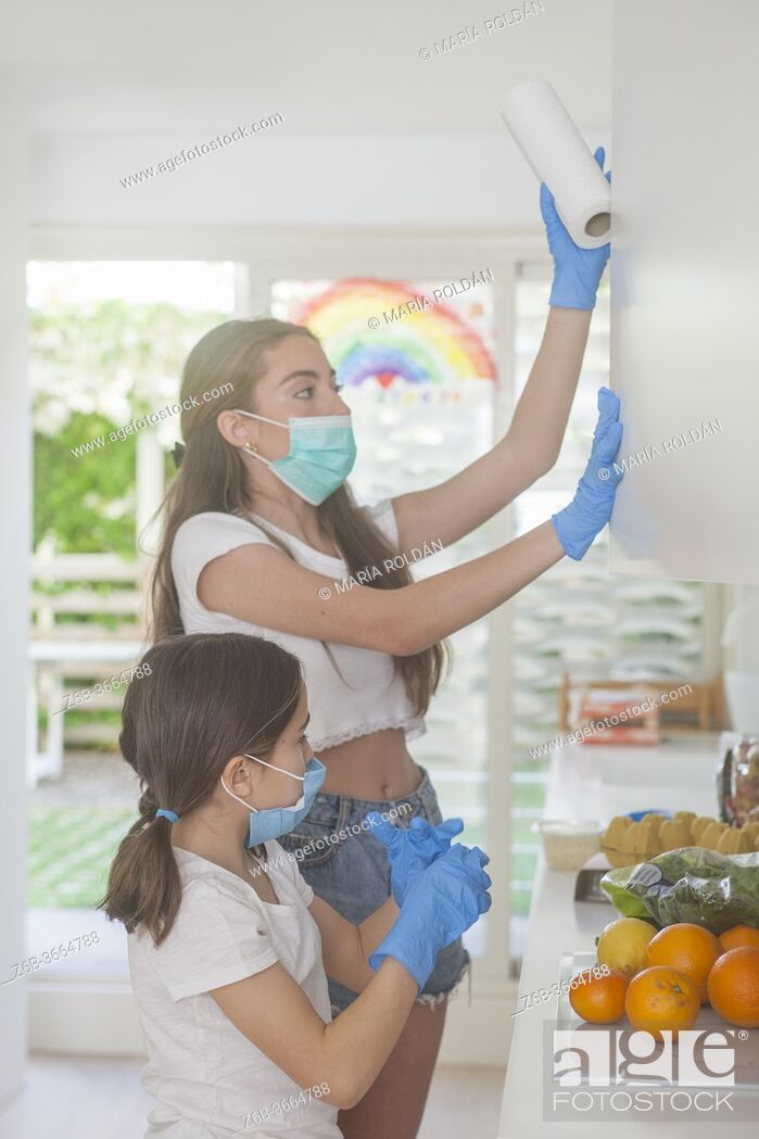 Photo de stock: mother and daughter with masks and gloves in kitchen.