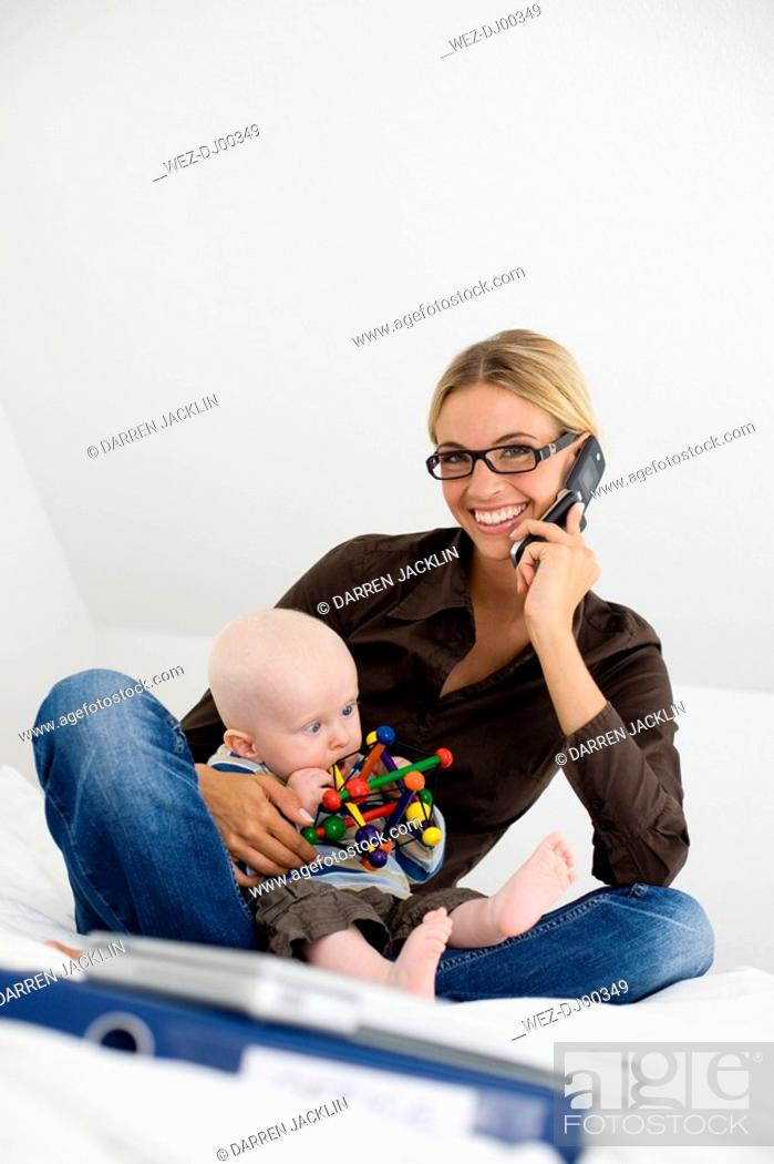 Stock Photo: Germany, Ammersee, Diessen, Young woman with baby boy 7 months on bed, using mobile phone.