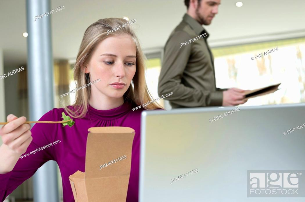 Stock Photo: Businesswoman taking salad while working in the home office.