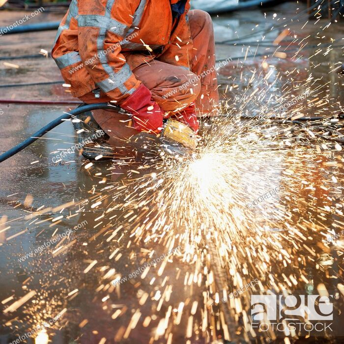 Stock Photo: Sparks flying off a grinding machine towards the camera, smoothing the welds on a steel ship deck.