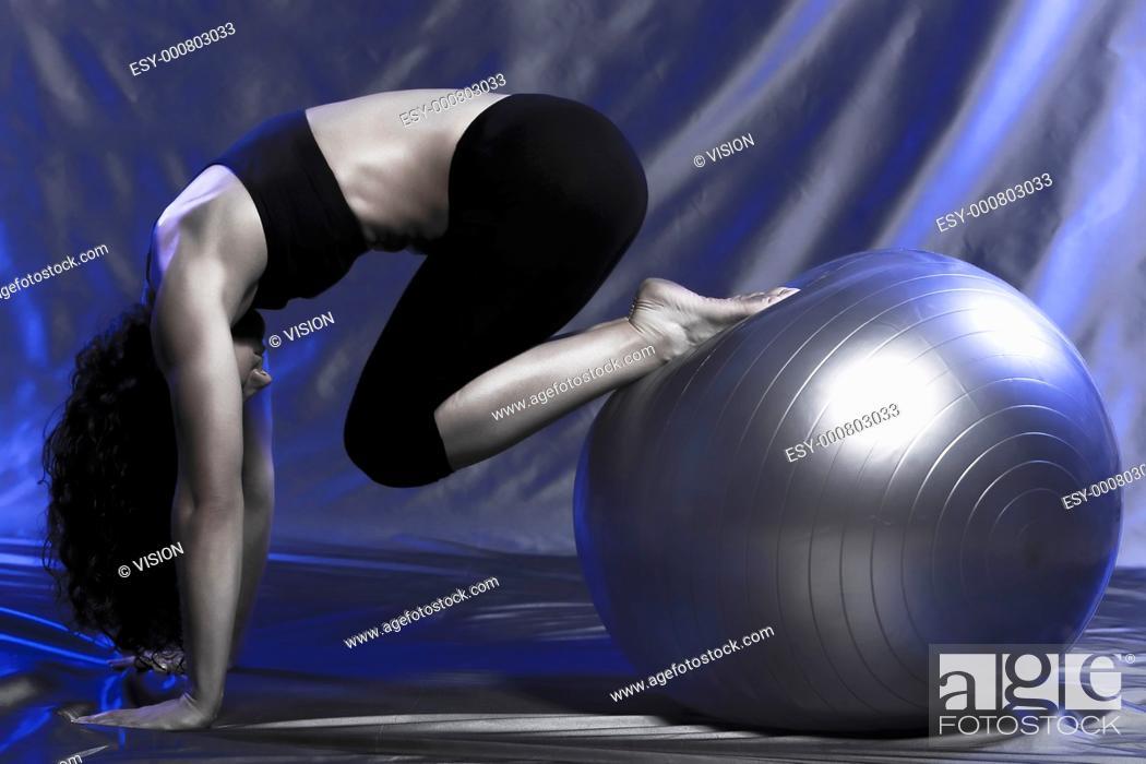 Stock Photo: young woman exercising swiss ball studio.