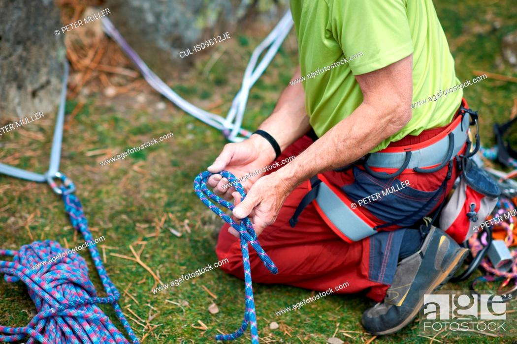 Stock Photo: Cropped view of rock climber preparing climbing rope.