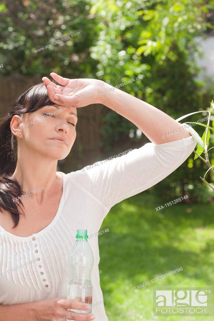 Imagen: Woman drinking water in garden.