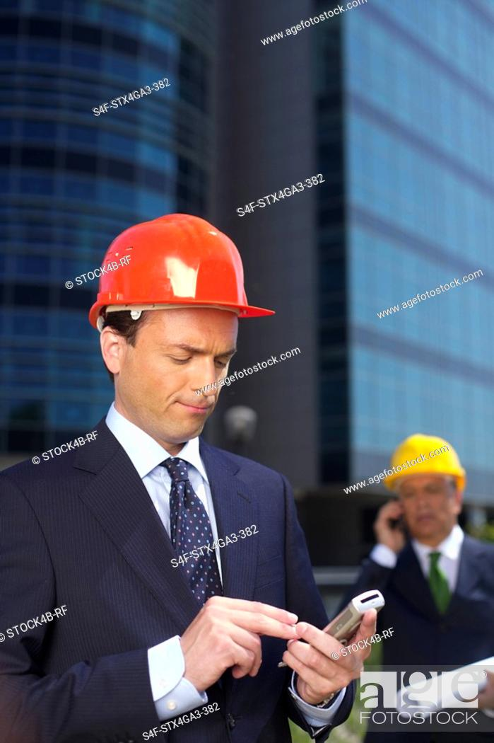 Stock Photo: Businessman with hardhat using a mobile phone.