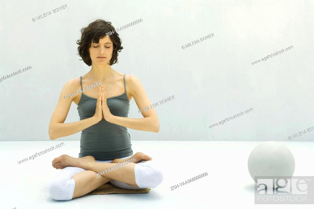 Stock Photo: Woman sitting on the ground in lotus position, hands clasped, eyes closed.