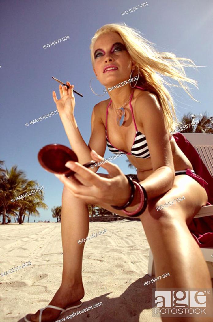 Stock Photo: Woman applying cosmetics on beach.