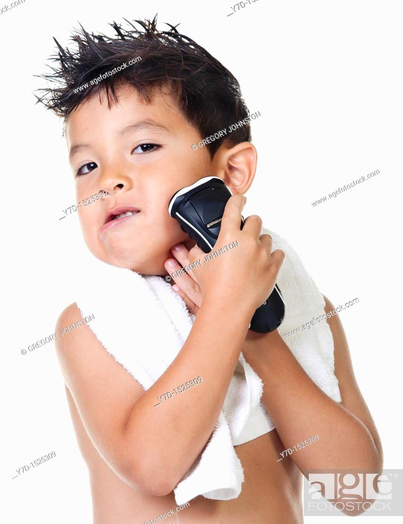 Stock Photo: A young boy has fun pretending to shave with an electric razor.