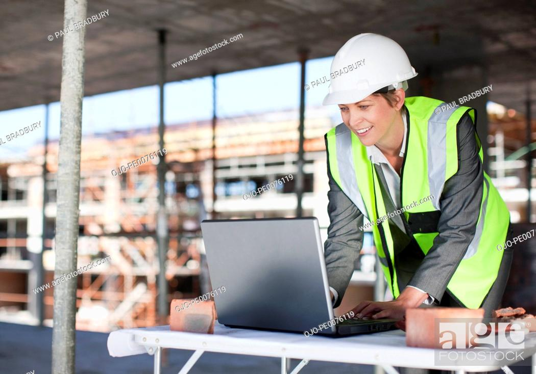 Stock Photo: Construction worker using laptop on construction site.