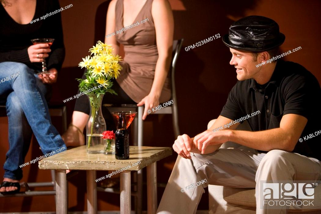 Stock Photo: Portrait of smiling young man in black hat sitting and having drinks with friends in modern living room.
