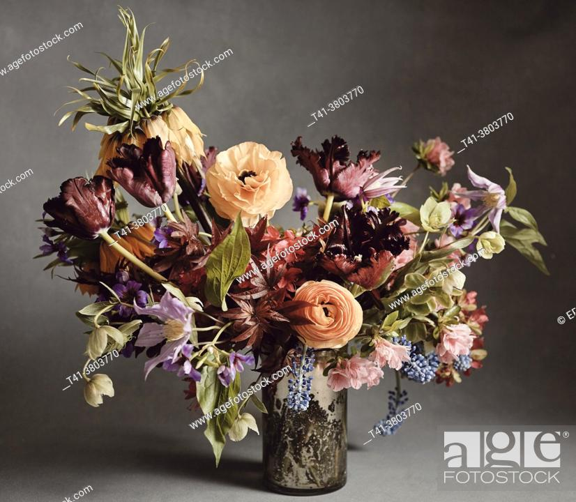Stock Photo: A bouquet of red, orange, purple, green and blue flowers in a mercury glass vase against a grey backdrop.