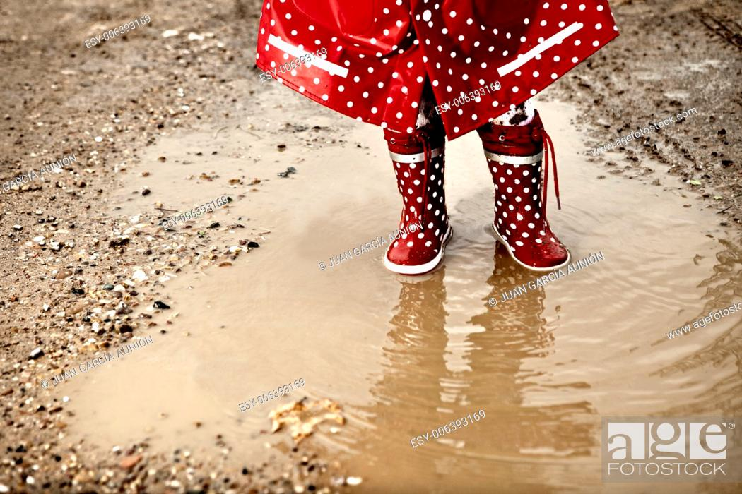 Stock Photo: Detail of rainboots of a baby girl dressed with dotted raincoat in the puddles.
