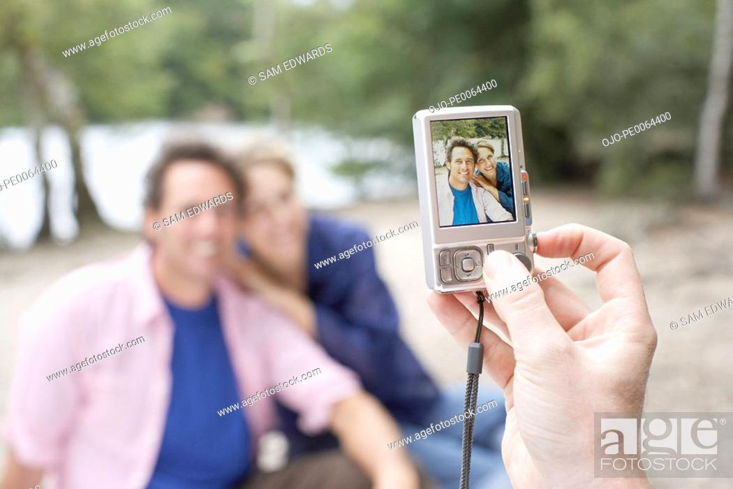 Stock Photo: Couple having photograph taken with camera.