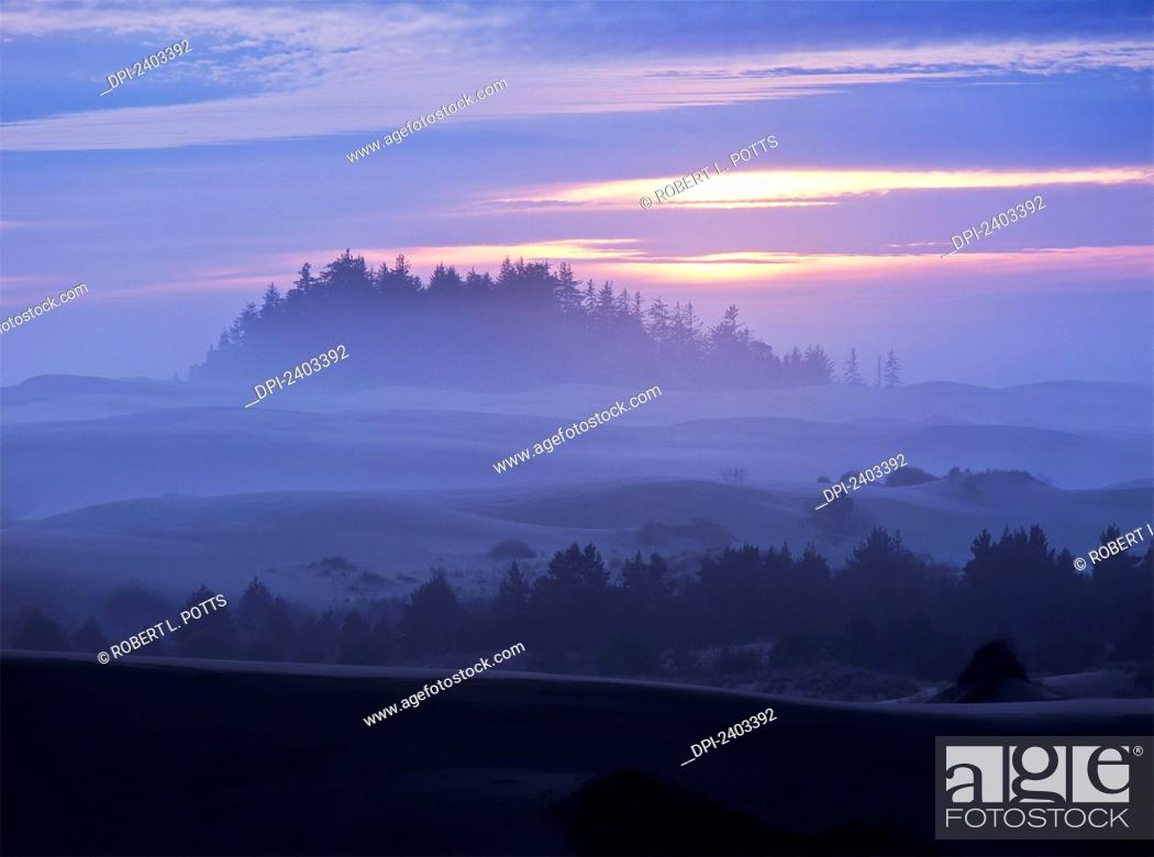 Stock Photo: The sun sinks low at sunset with a fog covered landscape; Lakeside, Oregon, United.