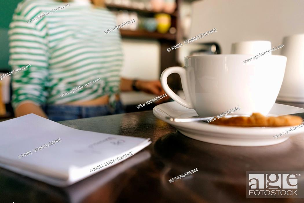 Stock Photo: Cup of coffee and notepad on table in a cafe with woman in background.