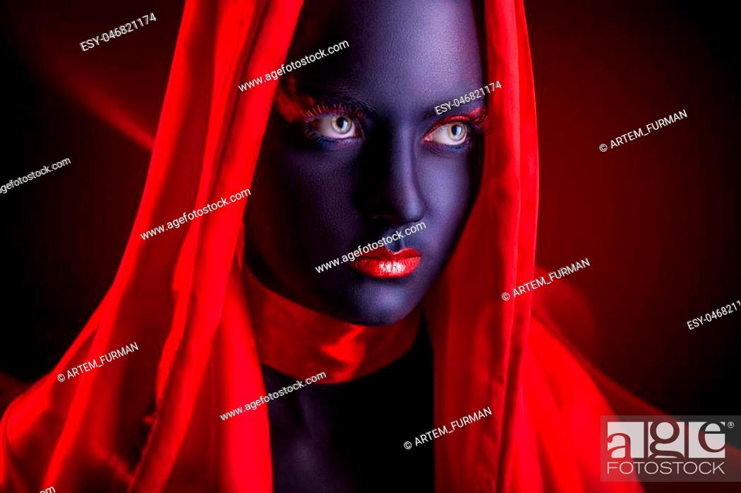 Stock Photo: Young woman in a red cape with black makeup on a dark background.