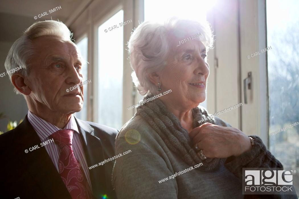 Stock Photo: A senior couple looking out a window at the view.