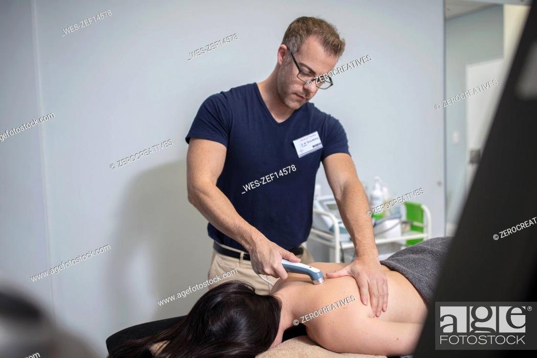 Stock Photo: Physio massaging woman's back with a device.