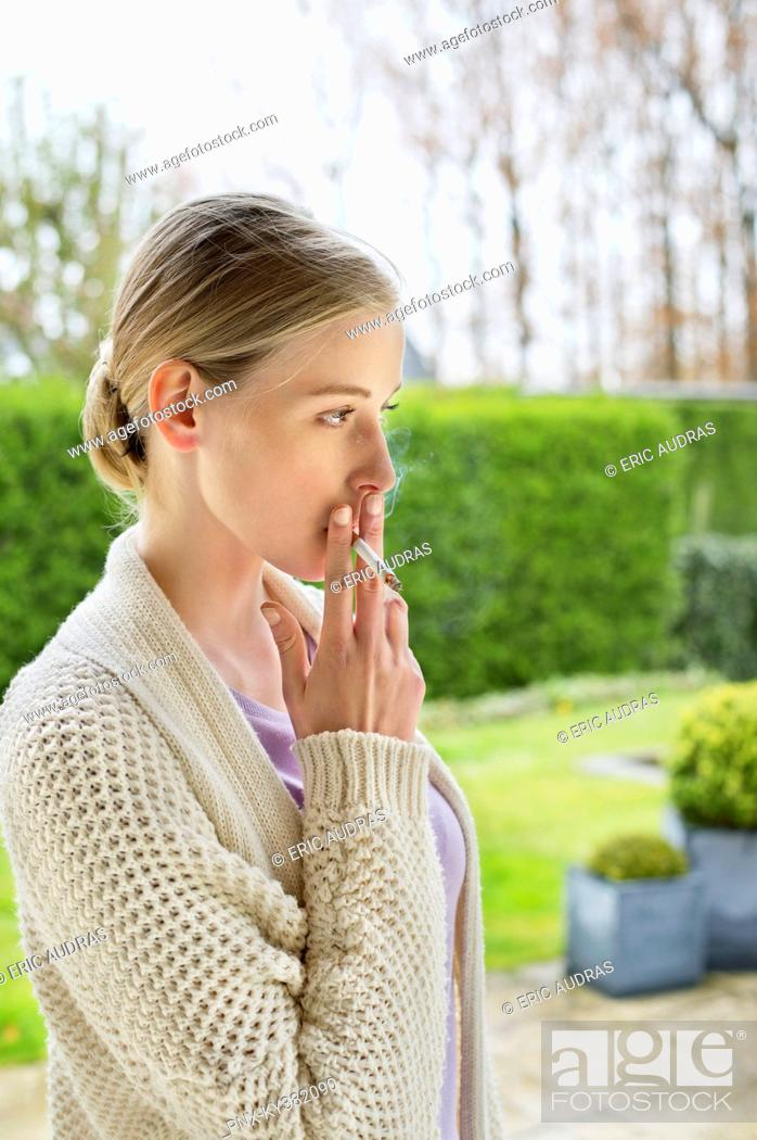 Stock Photo: Woman smoking cigarette in park.