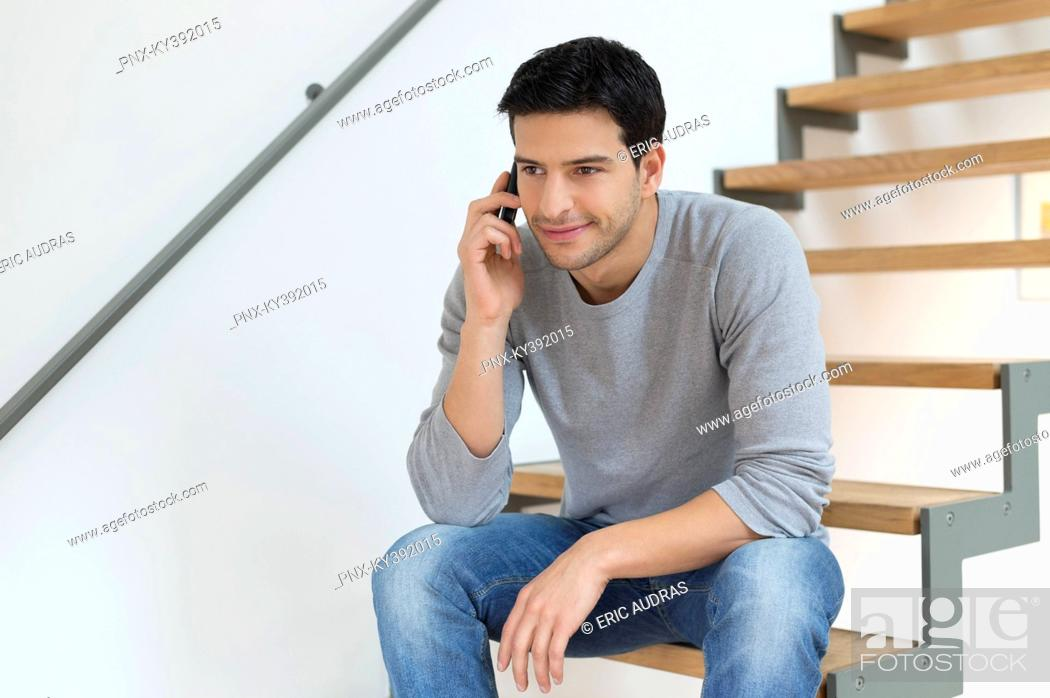 Stock Photo: Man sitting on stairs and talking on a mobile phone.