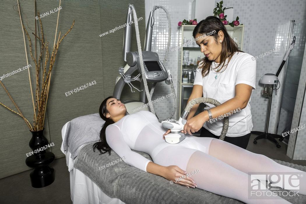 Stock Photo: Adult professional masseur giving massage to young woman with contemporary circulatory equipment.