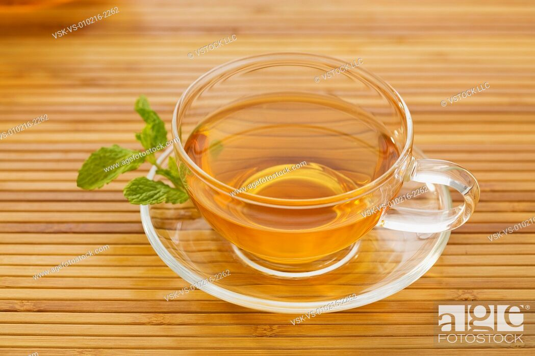 Imagen: Tea in cup with mint leaf on saucer.