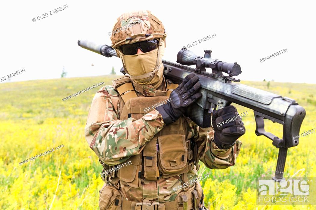 Imagen: Special forces soldier walks across the yellow field with sniper rifle close up.