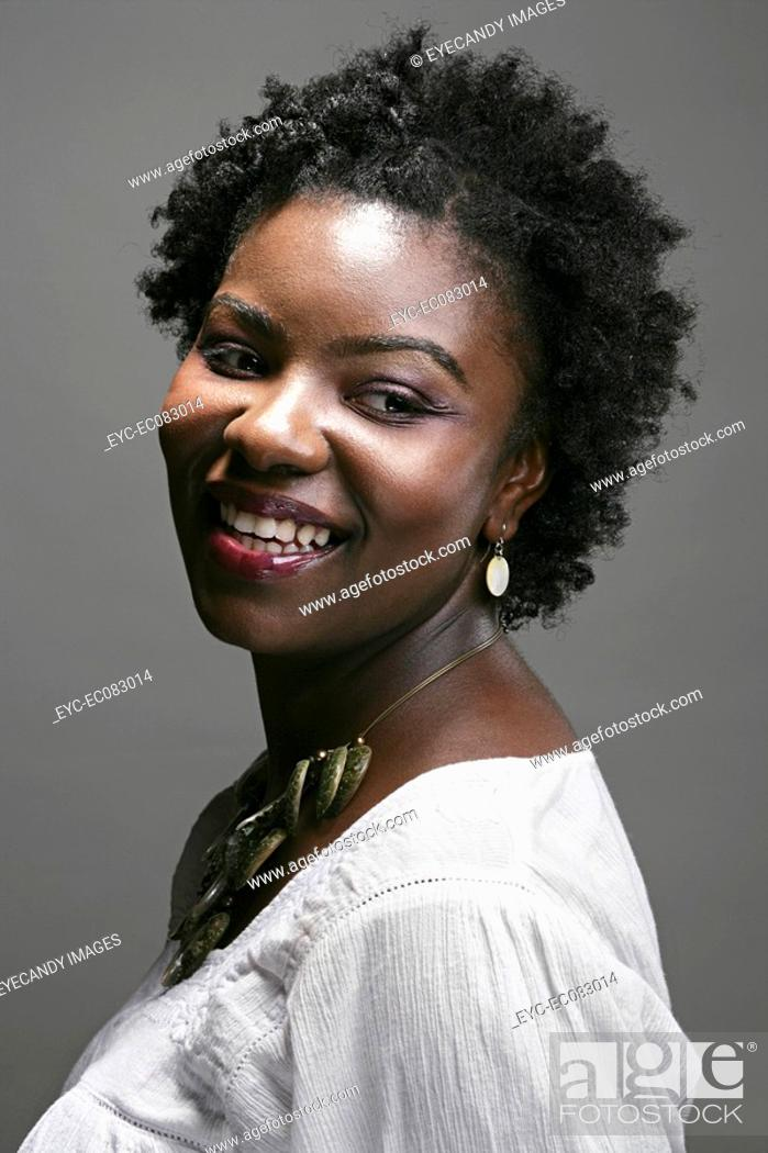 Stock Photo: Portrait of young happy African American woman, studio shot.