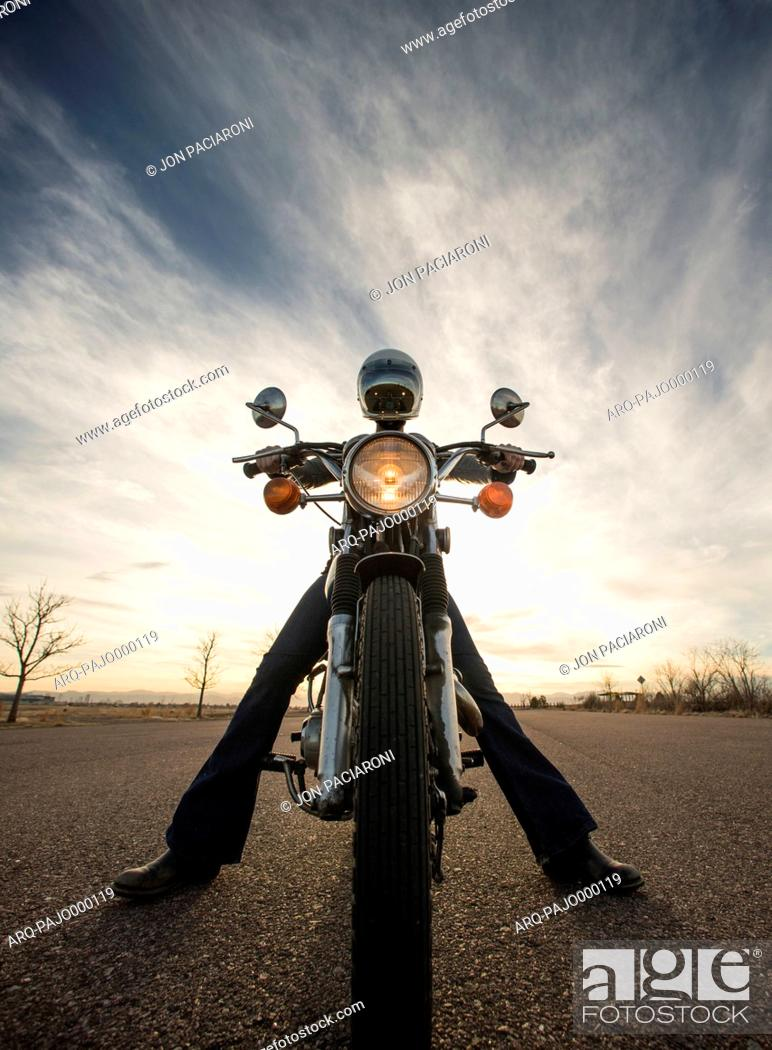 Imagen: Centered perspective of a woman sitting on her vintage motorcycle wearing a reflective helmut face shield with the sun setting in the background.