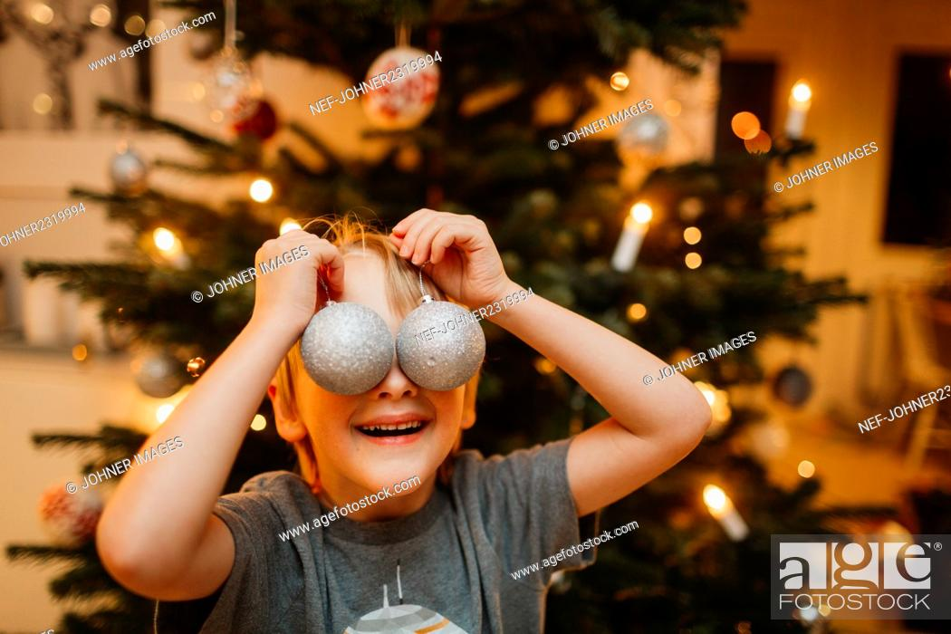 Stock Photo: Boy playing with Christmas ornaments.