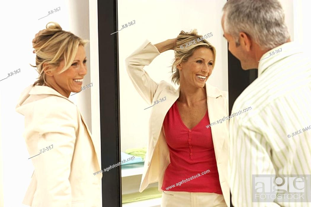 Stock Photo: Woman trying on new clothes in fitting room, hand in hair, reflection in mirror, husband looking on.